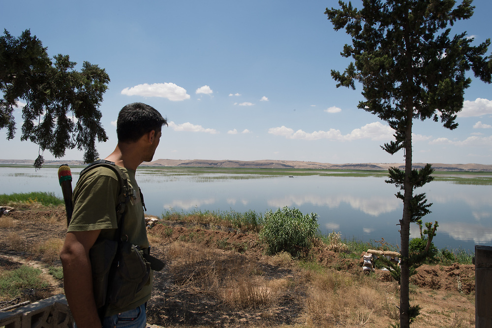 A fighter of YPG is looking in the direction of ISIS territory, which lies on the other side of Euphrat. Kobanê (Ayn al-Arab), Syria, June 15, 2015