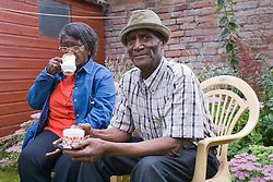 Older couple sitting  in their garden and enjoying a cup of coffee,