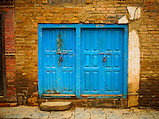 31 JULY 2015 - KATHMANDU, NEPAL:  Blue doors in an ancient brick wall at Swayambhunath Stupa, a large Buddhist stupa in Kathmandu. Parts of the stupa were badly damaged in the Nepal earthquake of 2015 but it is still open for religious devotees and tourists. Construction of the stupa started in the 1600s.   PHOTO BY JACK KURTZ
