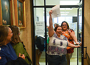 Gary Cosby Jr./Decatur Daily     Gay couples line up to get their marriage licenses in the Madison County Courthouse in Huntsville Monday.  Eleanor Shue lifts her marriage license and yells in celebration as she and partner Jessica White emerge from the Probate Judges office.