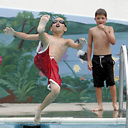 Harrison, NY / 2007 - Anthony Tiso jumps into the pool while friend Andrew Abbattista watches at West Harrison's John A. Passidomo Veteran's Park.  ( Mike Roy / The Journal News )