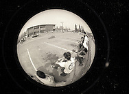 Skateboarders, seen through a fisheye conversion lens,  compete in a vert skateboarding contest on a half-pipe at the YMCA around the spring of 1988 in Visalia, California.