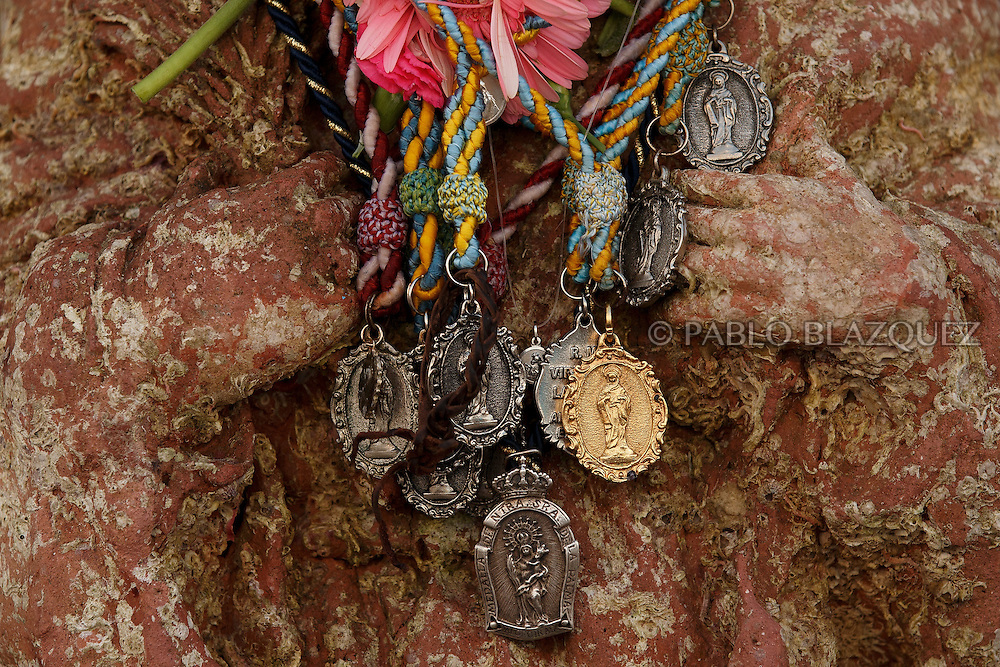 15/08/2016. Necklaces left by worshippers hold from the Virgin of Palm image during the yearly Virgin of Palm maritime pilgrimage at El Rinconcillo beach on August 15, 2016 in Algeciras, Spain. The Our Lady of Palm maritime pilgrimage in Algeciras dates back to 1975 and takes place annually when fishermen rescue the submerged virgin from the deep sea. Worshippers amid thousands of visitors await its arrival at the Rinconcillo beach. The devotion for the Virgin of Palm comes from the seventeenth century when a ship coming from Italy docked at Algeciras port to wait out bad weather. According to legend, once the crew of the ship removed a box with an image of the Virgin from its cargo the weather turned and the sea's tides were calmed. (© Pablo Blazquez)