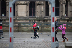 © Licensed to London News Pictures . 25/12/2018 . Manchester , UK . A man carrying a sleeping bag over his shoulder crosses Albert Square . Homeless people sleeping rough on the streets of Manchester City Centre on Christmas Day . Photo credit : Joel Goodman/LNP
