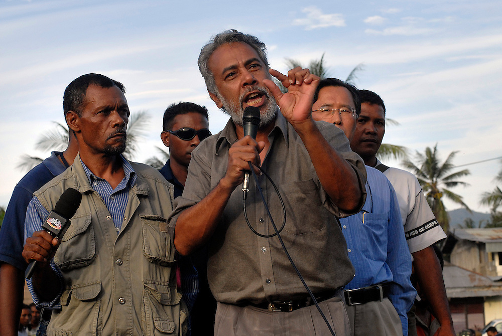 """Some 2,000 protesters in trucks, buses and on motorbikes shouted """"bring down Some 2,000 protesters in trucks, buses and on motorbikes shouted """"bring down Alkatiri"""" and voiced support for President Xanana Gusmao as they entered Dili escorted by international peacekeepers. Gusmao asked them to return to their own places and called for an end to the violence. After hours of travel and delays, hearing from Xanana and Protest spokesman Major Augusto de Araujo Tara (Xanana's immediate right) seemingly satisfied the protestors and they returned home under peacekeeper escort. 060606"""