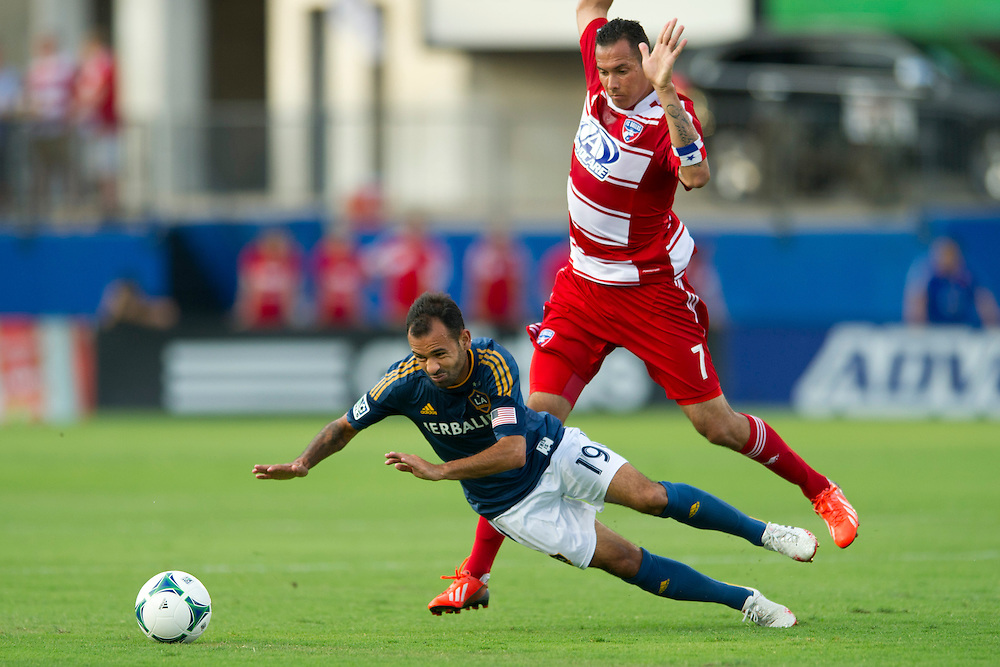 FRISCO, TX - AUGUST 11:  Juninho #19 of the Los Angeles Galaxy falls to the ground in front of Blas Perez #7 of FC Dallas on August 11, 2013 at FC Dallas Stadium in Frisco, Texas.  (Photo by Cooper Neill/Getty Images) *** Local Caption *** Juninho; Blas Perez