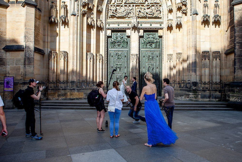 """A """"just married"""" couple getting photographed in front of St. Vitus Cathedral in Prague. The house of worship is a Roman Catholic metropolitan cathedral on the area of the Prague Castle complex and the seat of the Archbishop of Prague."""