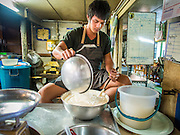 "06 FEBRUARY 2015 - BANGKOK, THAILAND: A worker at Thanusingha Bakery mixes batter for traditional Thai Catholic desert cakes. The cakes are called ""Kanom Farang Kudeejeen"" or ""Chinese Monk Candy."" The tradition of baking the cakes, about the size of a cupcake or muffin, started in Siam (now Thailand) in the 17th century AD when Portuguese Catholic priests accompanied Portuguese soldiers who assisted the Siamese in their wars with Burma. Several hundred Siamese (Thai) Buddhists converted to Catholicism and started baking the cakes. When the Siamese Empire in Ayutthaya was sacked by the Burmese the Portuguese and Thai Catholics fled to Thonburi, in what is now Bangkok. The Portuguese established a Catholic church near the new Siamese capital. Now just three families bake the cakes, using a recipe that is 400 years old and contains eggs, wheat flour, sugar, water and raisins. The same family has been baking the cakes at the Thanusingha Bakery, near Santa Cruz Church, for more than five generations. There are still a large number of Thai Catholics living in the neighborhood around the church.        PHOTO BY JACK KURTZ"