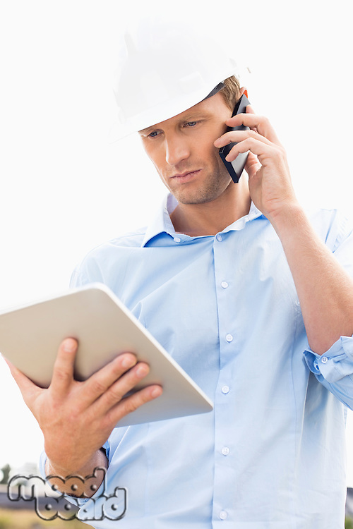 Male architect with digital tablet using cell phone at site
