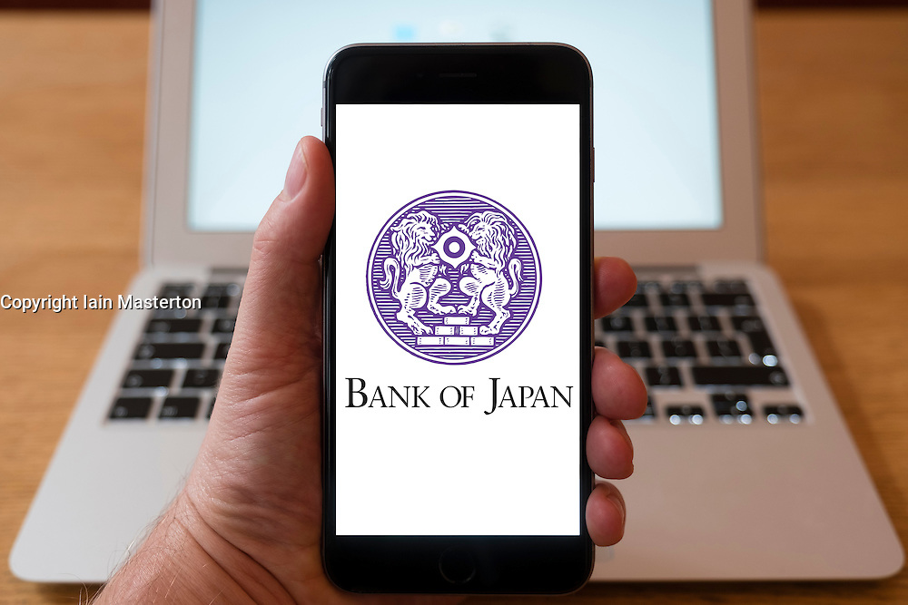 Using iPhone smartphone to display logo of the Bank of Japan, the central bank of Japan.
