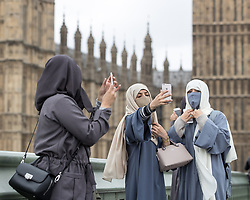© Licensed to London News Pictures . 29/03/2017 . London , UK . Three women wearing hijabs take selfies from Westminster Bridge outside Parliament in Westminster today (29th March 2017) . Photo credit : Joel Goodman/LNP