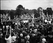 Funeral of Eamon DeValera.   (J72)..1975..02.09.1975..09.02.1975..2nd September 1975..Today saw the funeral of Eamon DeValera. He was laid to rest beside his wife Sinead in Glasnevin Cemetery,Dublin. Dignitries from all around the world attended at the funeral...Picture of the Tricolour draped coffin containing the mortal remains of Eamon DeValera approaching the grave side. The family of Mr DeValera following behind through the mass of mourners.