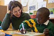 A young African boy practices writing with a volunteer teacher in a classroom in Observatory Primary School, Cape Town, South Africa.  The volunteer teacher has been provided to the school by Shine Centre which is a charity that aims to address the high illiteracy rate in South Africa by improving literacy levels among children in schools and disadvantaged communities.