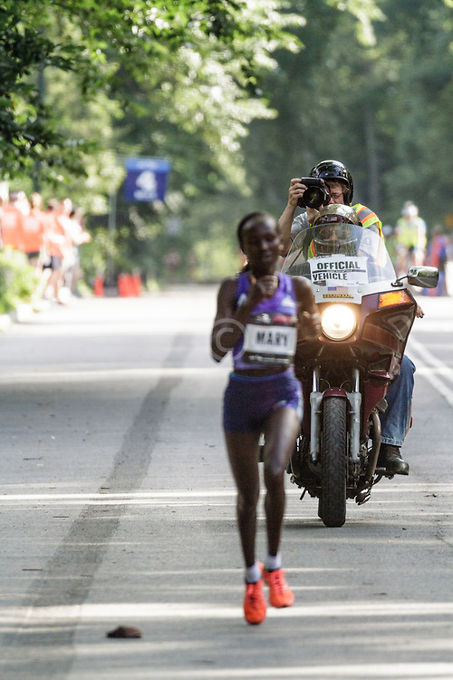 NYRR Oakley Mini 10K for Women: Victah Sailer on motorcycle photographs winner 31:15 Mary Keitany, Kenya, adidas