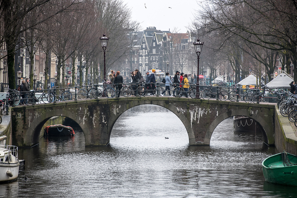 Group of individuals use bridge to cross canal that runs through the city of Amsterdam with historic canal houses in the background, Netherlands..