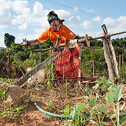 CAPTION: Emily retrieves water for her garden from a well, using a bucket. More borehole pumps mean more people will have easier access to water for household use, as well as for agriculture. LOCATION: Mandivingera Village, Bikita District, Masvingo Province, Zimbabwe. INDIVIDUAL(S) PHOTOGRAPHED: Emily Nhamo.