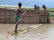 An unidentified village flood victim Farmer is trying to reach thier inundated house by floodwaters to save their family memebers, who sit on the roof, to a safer place at Sialmari, about 329 kilometers southwest of Gauhati, the capital city of Northeastern Indian state, Assam, Wednesday, June 30, 2004. ..Floodwaters of the Asia'a one of the largest river, Brahmaputra and its 35 tributaries have affected more than 2 million in all of South Asia and disrupted communication in many parts of the Indian subcontinent, sources said. (AP Photo/ Shib Shankar Chatterjee).