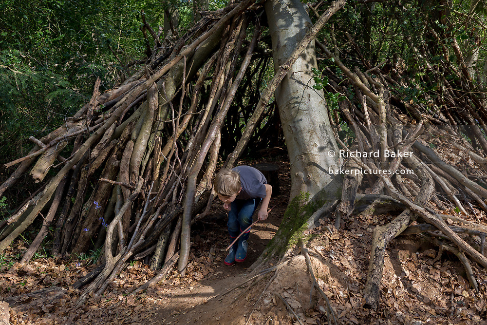 A seven year-old boy in woods plays on his own inside a wooden den, on 23rd April 2017, in Wrington, North Somerset, England.