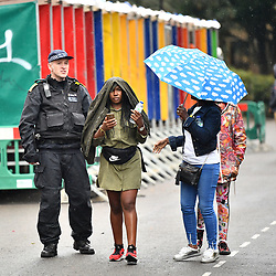 © Licensed to London News Pictures. 26/08/2018. London, UK. Carnival goers and members of the public are caught in a downpour of rain on family day of the 2018 Notting Hill Carnival. Up to 1 million people are expected to attend this weekend's event that is one of the worlds largest street festivals. Photo credit: Ben Cawthra/LNP