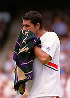 Mark Philippoussis (Australia) towels himself down between games. Wimbledon Tennis Championship, Day 13, 6/07/2003. Credit: Colorsport / Matthew Impey