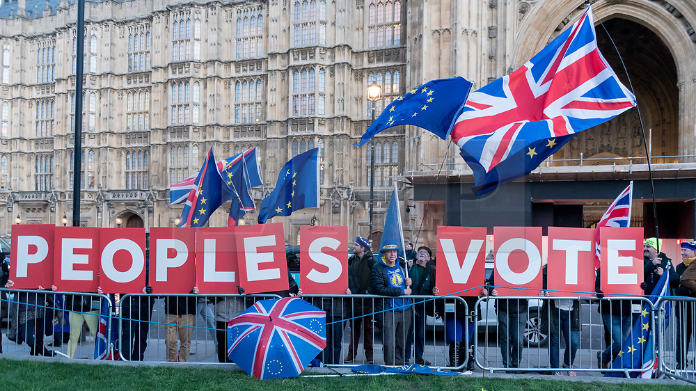 """© Licensed to London News Pictures. 11/12/2018. LONDON, UK. Steve Bray, founder of SODEM (Stand Of Defiance European Movement), stands amidst signs showing the words """"Peoples Vote"""" which are held up outside the House of Commons by anti-Brexit demonstrators. Theresa May, Prime Minister, is touring European capitals to try to renegotiate the Brexit agreement with the European Union after today's meaningful vote by MP's was deferred.  Photo credit: Stephen Chung/LNP"""