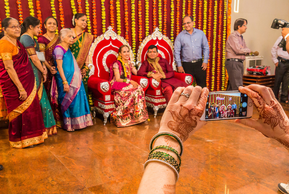 A womans hands holding a iPhone up to take pictures at an Indian wedding.