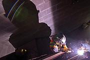 Jorge Rodrighez, a welder with Royal Oak Metal Craft, welds a hand rail to a stair stringer.