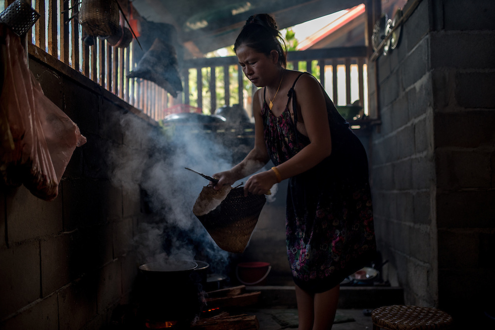 A woman prepares sticky rice in the village of Khoc Kham.