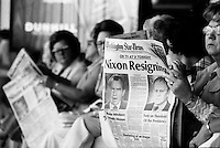 Women reading that Nixon is resigning, in the Washington airport