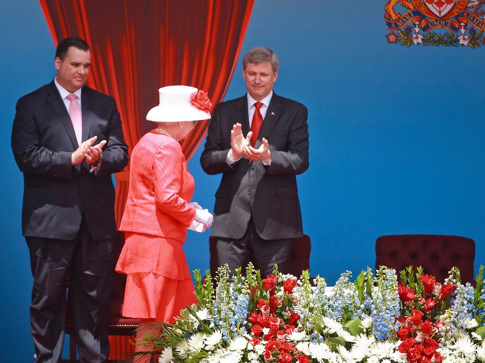 Canadian Prime Minister Stephen Harper, right, and Canada's Minister of Heritage, James Moore applaud following a speech by Queen Elizabeth II during Canada Day celebrations on Parliament Hill in Ottawa, Ontario, July 1, 2010. The Queen is on a 9 day visit to Canada. AFP/GEOFF ROBINS/STR