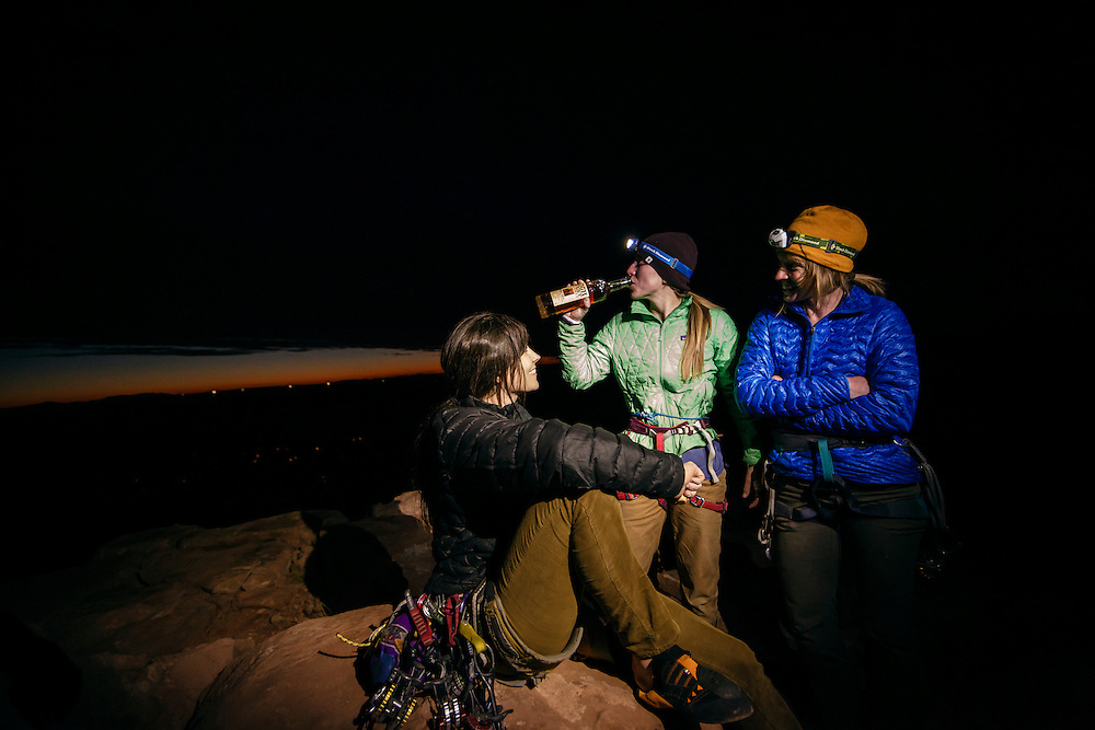 Julia Geisler, Kim Hall and Jewell Lund celebrate climbing Fine Jade, 5.11-, with a after sunset pull of whiskey.
