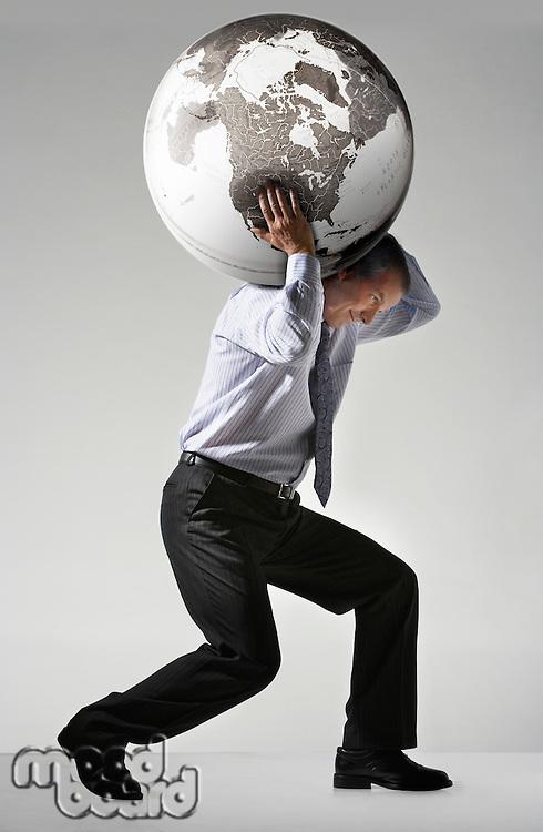 Businessman struggling carrying globe on shoulders side view