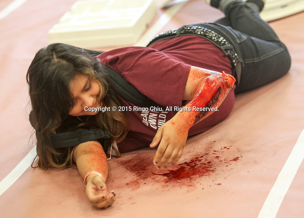 A mock victim waits for treatment during the annual Great California ShakeOut earthquake drill at Southern California University (USC) in Los Angeles on October 15, 2015. About 10.4 million Californian's registered to take part in the annual drill that asks participants to 'drop'' to the ground, take 'cover'' under a desk, table or other sturdy surface, and 'hold on'' for 60 seconds, as if a major earthquake were occurring.(Photo by Ringo Chiu/PHOTOFORMULA.com)