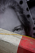 A woman's eye a construction site hoarding peers over the top of a timber traffic barrier and wiring.
