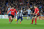 West Brom's Stephane Sessegnon © breaks away from Cardiff's Gary Medel (l) and Ben Turner (r). Barclays Premier league, Cardiff city v West Bromwich Albion at the Cardiff city Stadium in Cardiff, South Wales on Saturday 14th Dec 2013. pic by Andrew Orchard, Andrew Orchard sports photography.