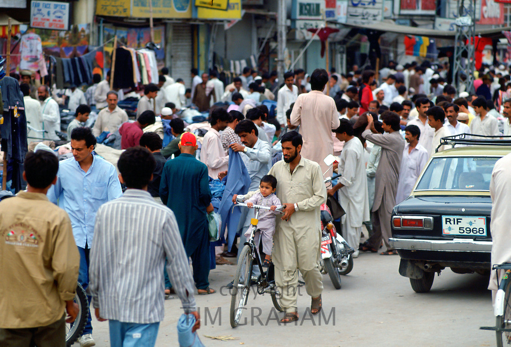Man wheeling  child on bicycle in crowded street in Islamabad in Pakistan