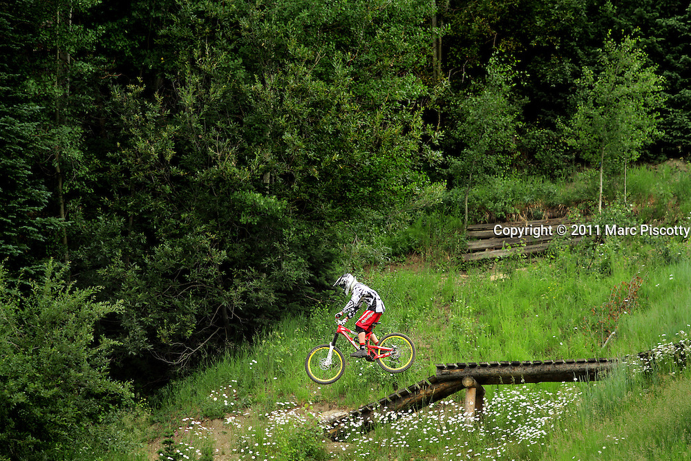 SHOT 7/28/11 3:13:30 PM - A mountain biker makes his way down a trail while riding in the Trestle Bike Park in Winter Park, Co. Featuring 37 miles of downhill trails accessed from three different chairlifts and over 200 features, the park offers programs for beginners to experts. (Photo by Marc Piscotty / © 2011)