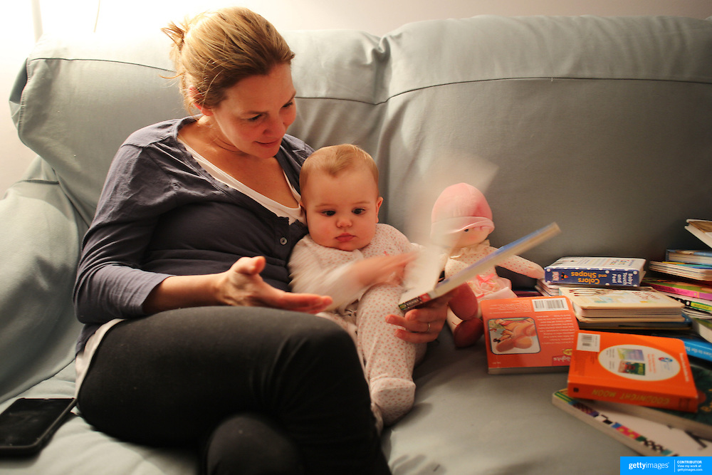 A mother reading books to her eight month old baby girl at bedtime. Photo Tim Clayton