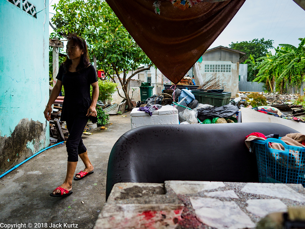 "22 MARCH 2018 - BANGKOK, THAILAND: A woman walks past demolished homes along Khlong Lat Phrao. Bangkok officials are evicting about 1,000 families who have set up homes along Khlong  Lat Phrao in Bangkok, the city says they are ""encroaching"" on the khlong. Although some of the families have been living along the khlong (Thai for ""canal"") for generations, they don't have title to the property, and the city considers them squatters. The city says the residents are being evicted so the city can build new embankments to control flooding. Most of the residents have agreed to leave, but negotiations over compensation are continuing for residents who can't afford to move.      PHOTO BY JACK KURTZ"