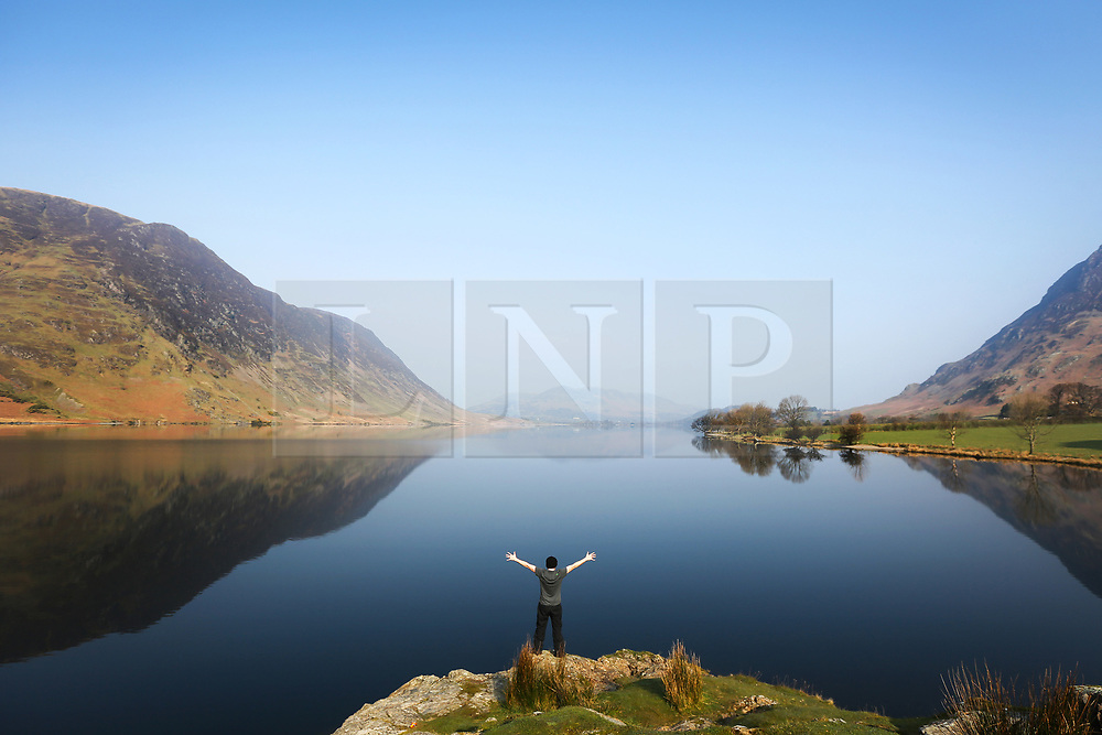 © Licensed to London News Pictures. 28/03/2017. Buttermere UK. A man stands above Crummock water in the Lake District this morning as the surrounding mountains reflect in the calm water on another sunny day in Cumbria. Photo credit: Andrew McCaren/LNP