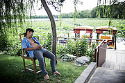 "A Chinese man takes a rest as he waits for clients for his boat rental activity at Summer Palace in Beijing, China, July 21, 2014. <br /> <br /> This image is part of the series ""24/7"", an ironic view on restless and fast-growing Chinese economy described through street vendors and workers sleeping during their commercial daily activity. <br /> <br /> © Giorgio Perottino"