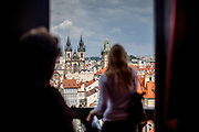 A woman is looking from the Jesuit College Clementinum Tower towards the Old Town Square Tower and Tyn Church, both located at Old Town Square.