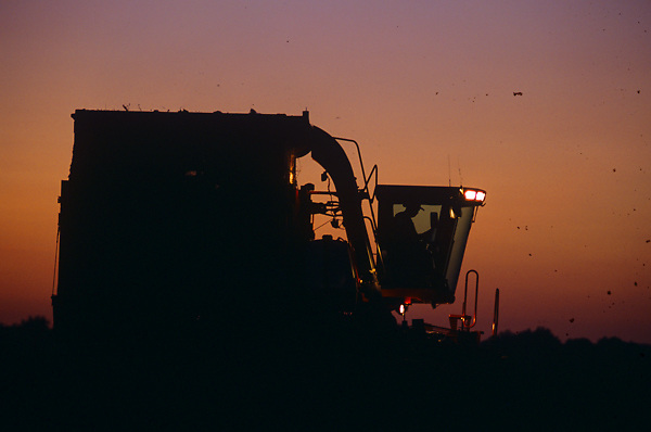 Stock photo of the silhouette of heavy farming machinery working at dusk