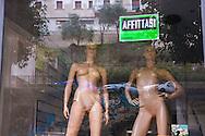 Sala Consilina, 10/02/2015: manichini nella vetrina di un negozio chiuso con il cartello affittasi