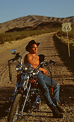 shirtless cowboy leaning on a motorcycle on Route 66 in the desert
