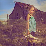 10-year-old girl holding skull outside the old homestead barn.
