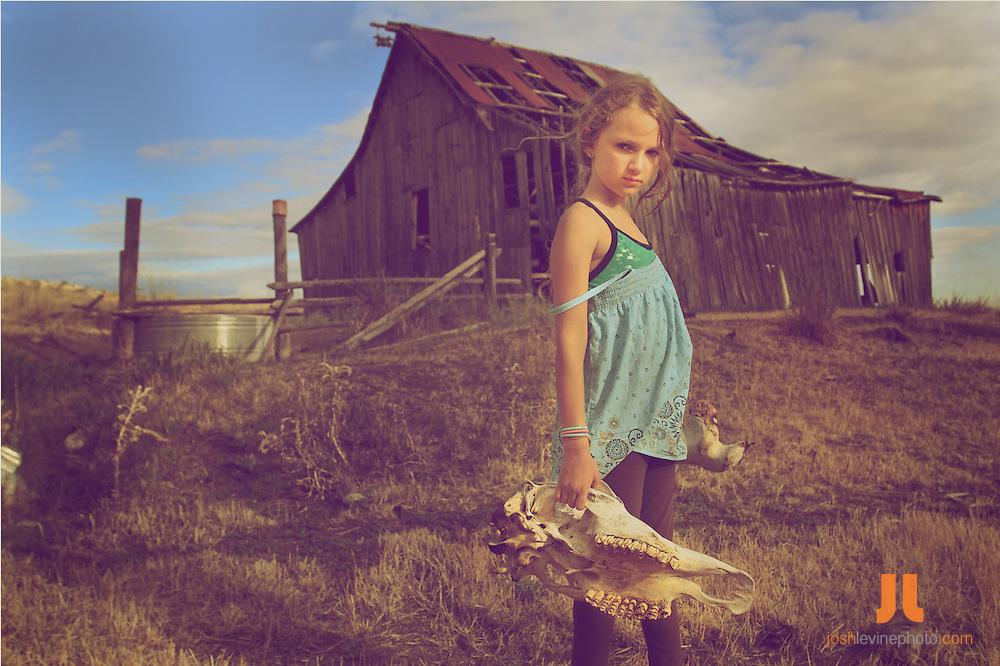 10-year-old girl holding skull outside the old homestead barn.