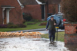 © Licensed to London News Pictures. 10/02/2014. Datchet, Berkshire, UK. A man wading through flood water during a heavy shower. Flooding in Datchet today, 10th February 2014 after the River Thames burst its banks. Photo credit : Rob Arnold/LNP