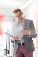 Businessman reading documents in creative office