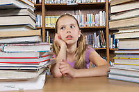 School girl sitting at desk with books in library